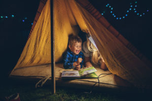 Portrait of a mother and son camping in an improvised tent in their backyard